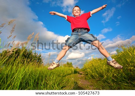 boy jumping on the meadow against the blue sky background