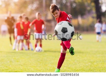Boy kicking football on the sports field during soccer match #1028981656