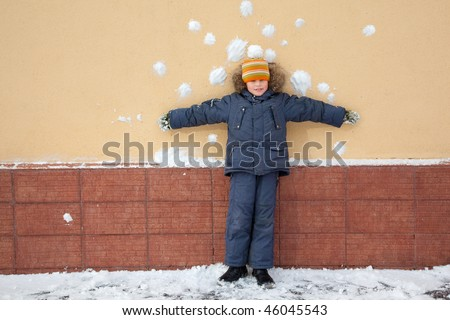 boy kid is standing near wall with snowballs snow stains. Risky bombardment shooting of defenceless boy by snowballs near wall