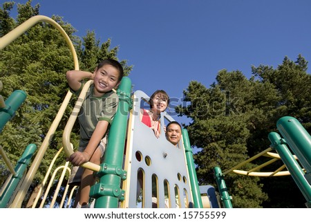 Boy leans on bar smiling at camera. Mother and father smile from background. Horizontally framed photo.
