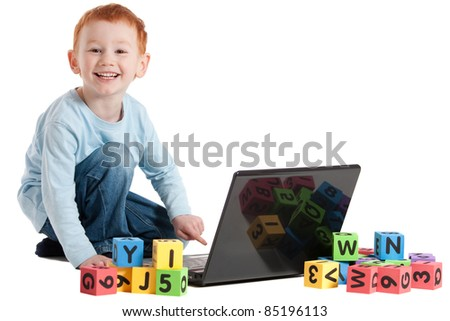 Boy learning reading with notebook computer and kids blocks. Isolated on white.
