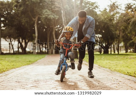 Boy learning to ride a bicycle with his father in park. Father teaching his son cycling at park.