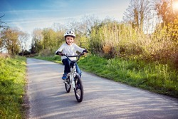 Boy learning to ride his bike on a country track road concept for safety and child development