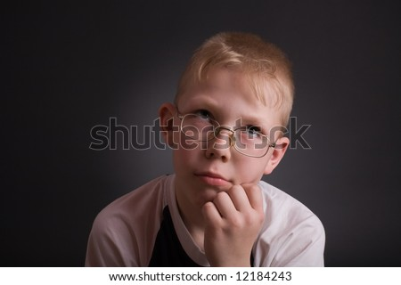 Boy look up and prop his head by hand in puzzlement as if pondering a deep question. Over grey background.