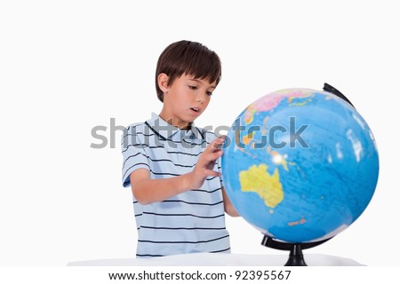 Boy looking at a globe against a white background