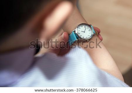 Boy looking at his wrist kid watch