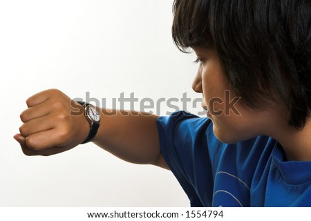 Boy looking at his wrist watch - stock photo