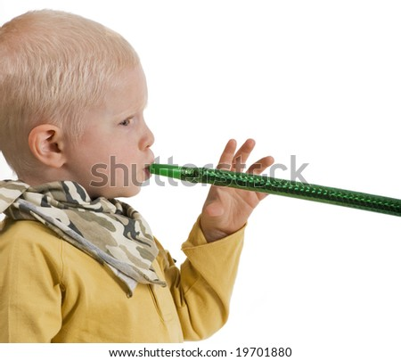 boy looking at viewer blowing noisemaker - stock photo