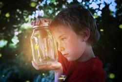 Boy looking into a jar of fireflies