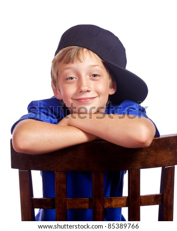 Boy looking over the back of a chair with a smile on his face and a baseball hat sitting sideways on his head.