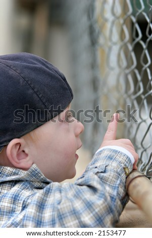 boy looking through a chain link fence and pointing at something of interest