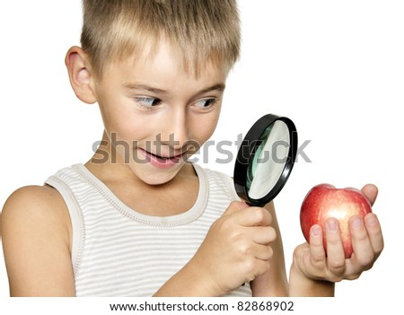 Boy  looking through a magnifying glass on apple in his hand. Isolated on white.
