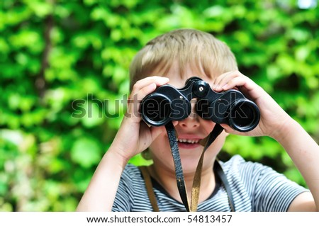 Boy looking through binocular in selective focus