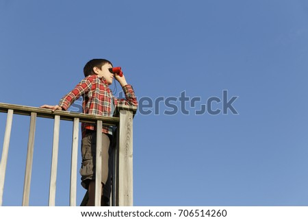 boy looking through binoculars outdoors. child standing by the wooden railing and holding binoculars on a background of blue sky. Copy space for your text Stockfoto ©