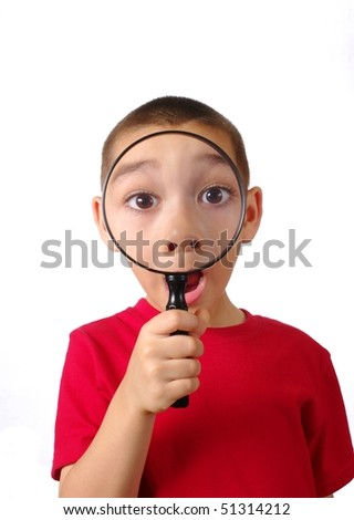 Boy looking through magnifying glass, isolated on white background