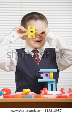 Boy looking through yellow toy block