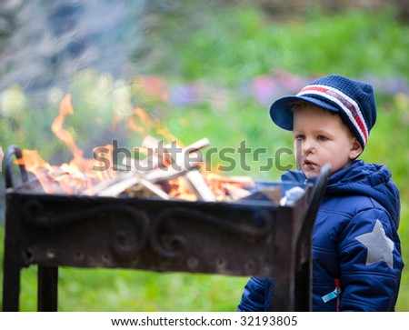 Boy looking to old style metal campfire made ready for grilling
