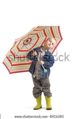 Boy looking up from under his umbrella to check the weather. - stock photo