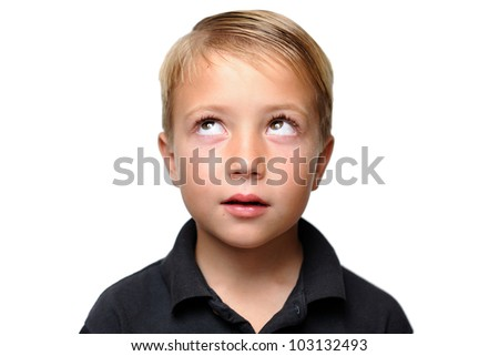 Boy Looking Upward While Thinking. Young boy facing camera with his eyes looking upward as if he is thinking.