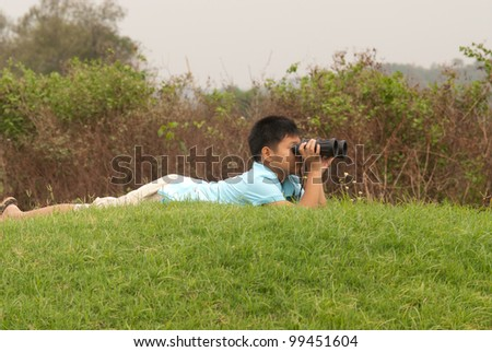 Boy looks into binoculars lying on top of hill .