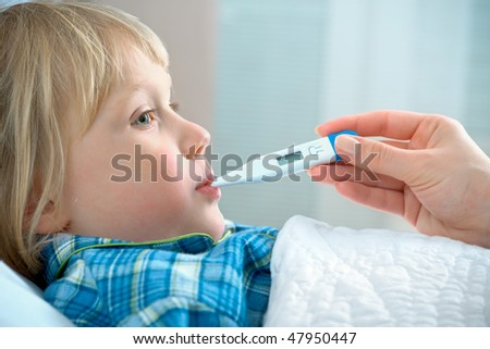 boy lying in bed with a thermometer