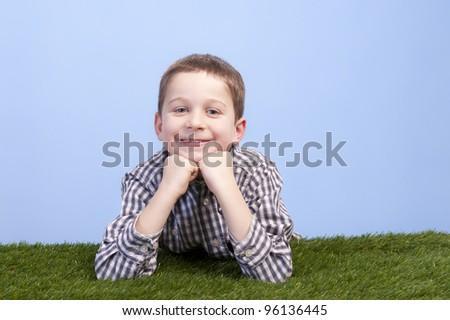 boy lying on a grass field against a blue sky