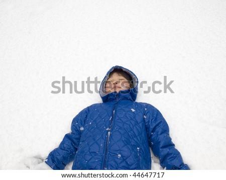 Boy lying on snow