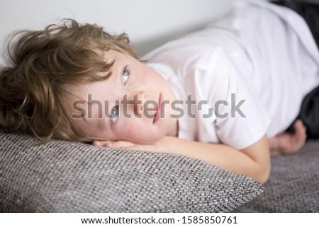 Boy lying on sofa, looking up