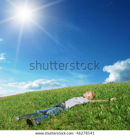 Boy lying on the grass. - stock photo