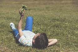 Boy lying on the grass playing with a toy airplane