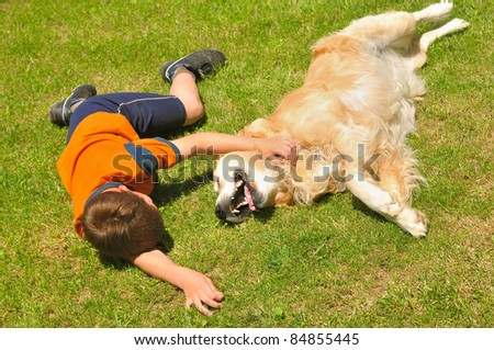 Boy lying with dog on green grass in park