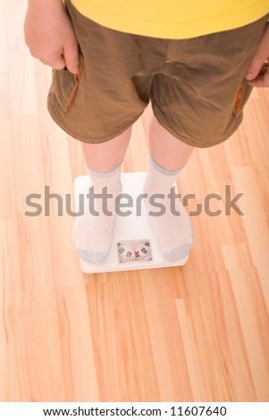 Boy measures weight on floor scales. Legs in shorts and socks standing at floor scales on hardwood floor in living room. View from above.