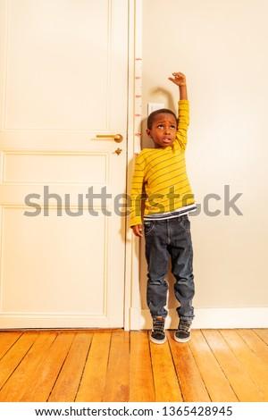 boy measuring his height benchmark on door at home