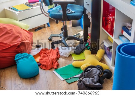 Boy messy bedroom with clothes and colorful pillows on the floor