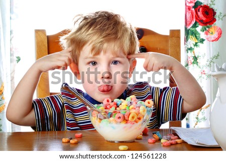 Boy misbehaving while eating breakfast cereal