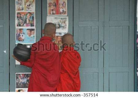 boy monks in burma looking at movie posters  after taking a break from seeking alms