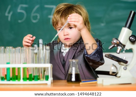 Boy near microscope and test tubes in school classroom. Science concept. Gifted child and wunderkind. Kid study chemistry school. School education. Explore biological molecules. Toddler genius baby.