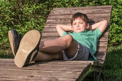 Boy of 8 years in T-shirt and shorts lies on wooden deck chair in the sun against background of green leaves. The boy in relaxed, lazy position, narrowed his eyes.