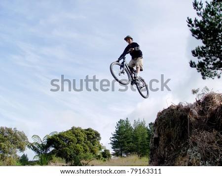 Boy on a bmx bike mid jump high in the air