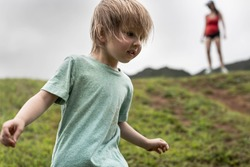 Boy on a hike is walking a risky path ahead of his mom