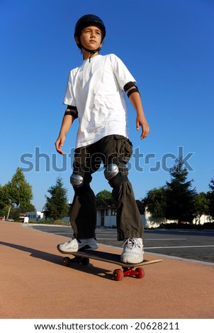 Boy on a skateboard against blue sky looking in the sun