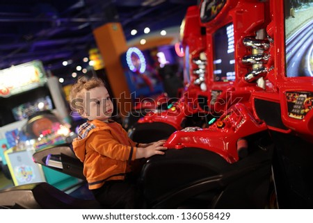 Boy on amusement bike at indoor playground