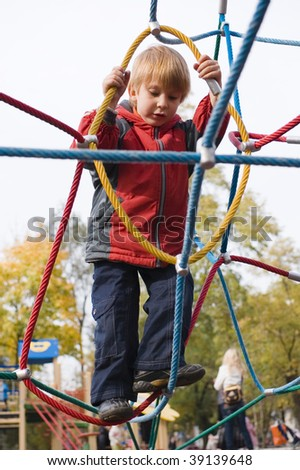 boy on playground climbing net of ropes