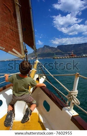 Boy on red-sail yacht's desk heading towards Table Mountain. Shot during yacht cruise in Waterfront, Cape Town, South Africa.