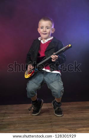 boy on stage with smoke, playing the guitar