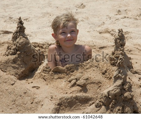 boy on the beach buried in sand on a summer day