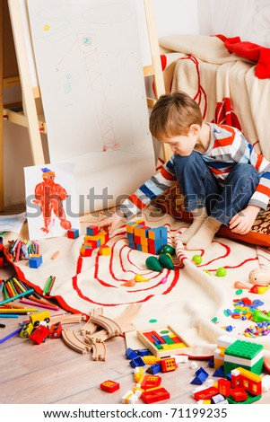boy on the floor plays varicoloured blocks