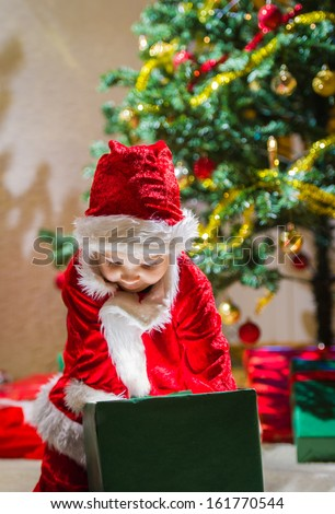 Boy opens a Christmas gift box, Christmas tree and gifts on background