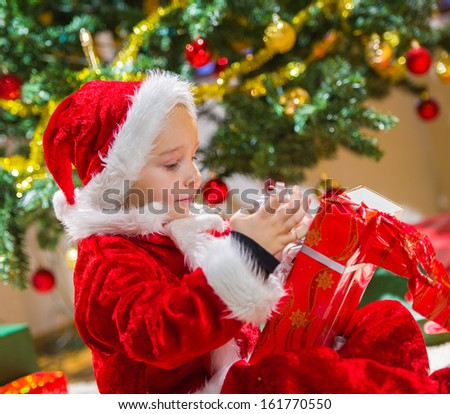 Boy opens a Christmas gift, Christmas tree and gifts on background