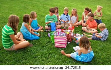 Boy opens birthday present with children gathered around